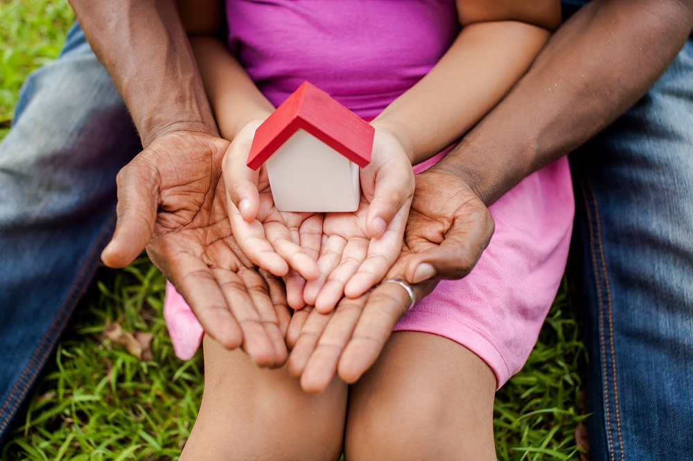 father and daughter holding a miniature house in their hands