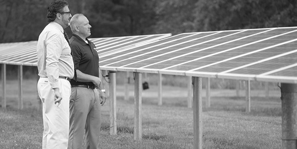 BankFive Commercial Lender Paul Medeiros and a BankFive business loan customer standing alongside solar panels at a solar farm