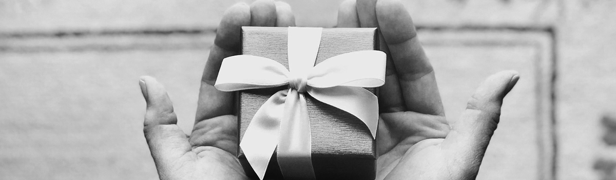 hands holding a square gift box with a bow