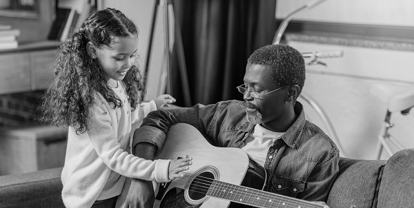grandfather and granddaughter practicing guitar in their own home