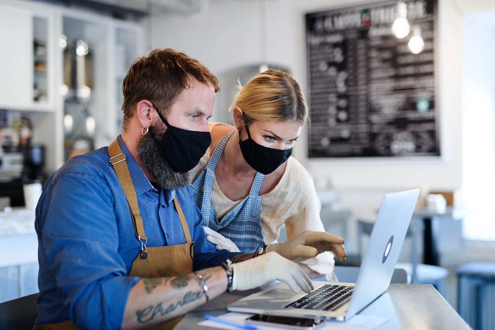 Male and female small businesses owners working on laptop