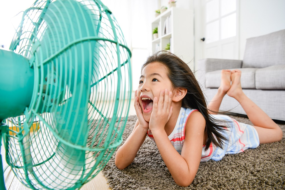 young girl laying on floor of home laughing into the breeze from a cooling fan
