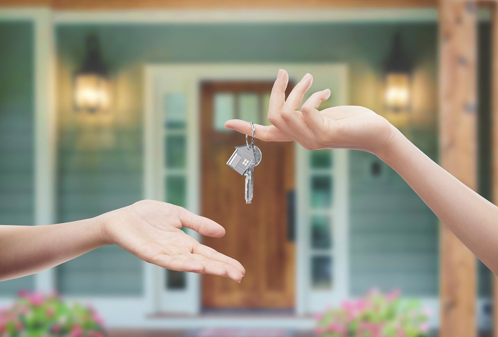 home buyer with their hand out getting the key to their new home