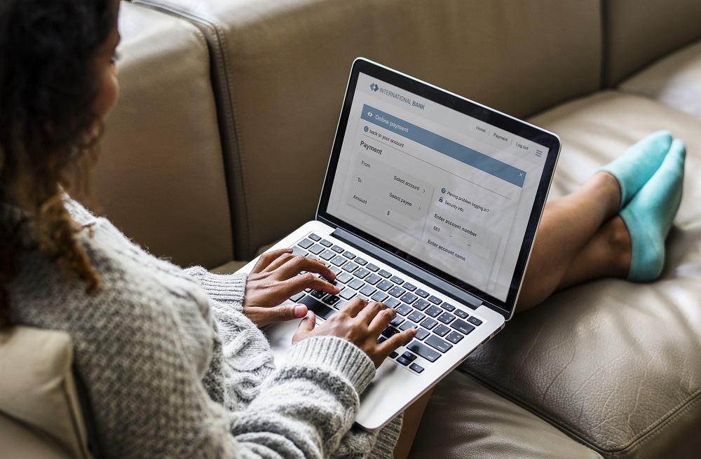 woman sitting on couch using online banking on her laptop