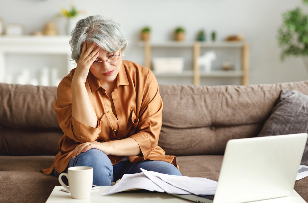 stressed woman at a coffee table with her laptop and a pile of bills