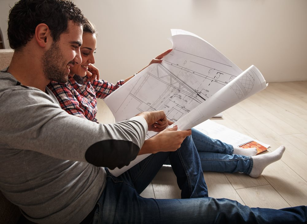 Man and women sitting on the floor holding a blue print drawing of a house