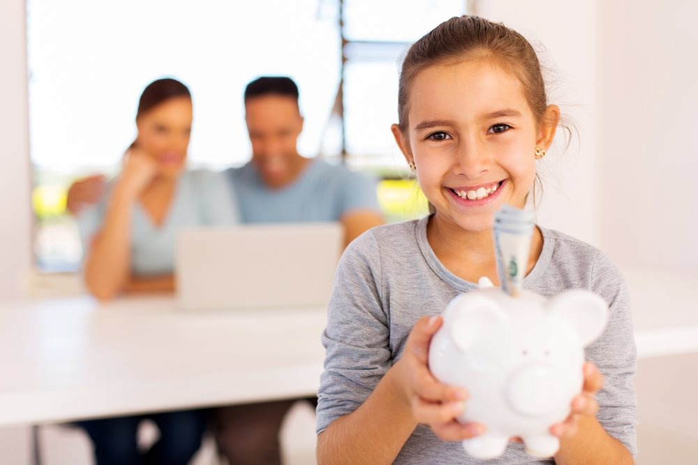 kid smiling with piggy bank