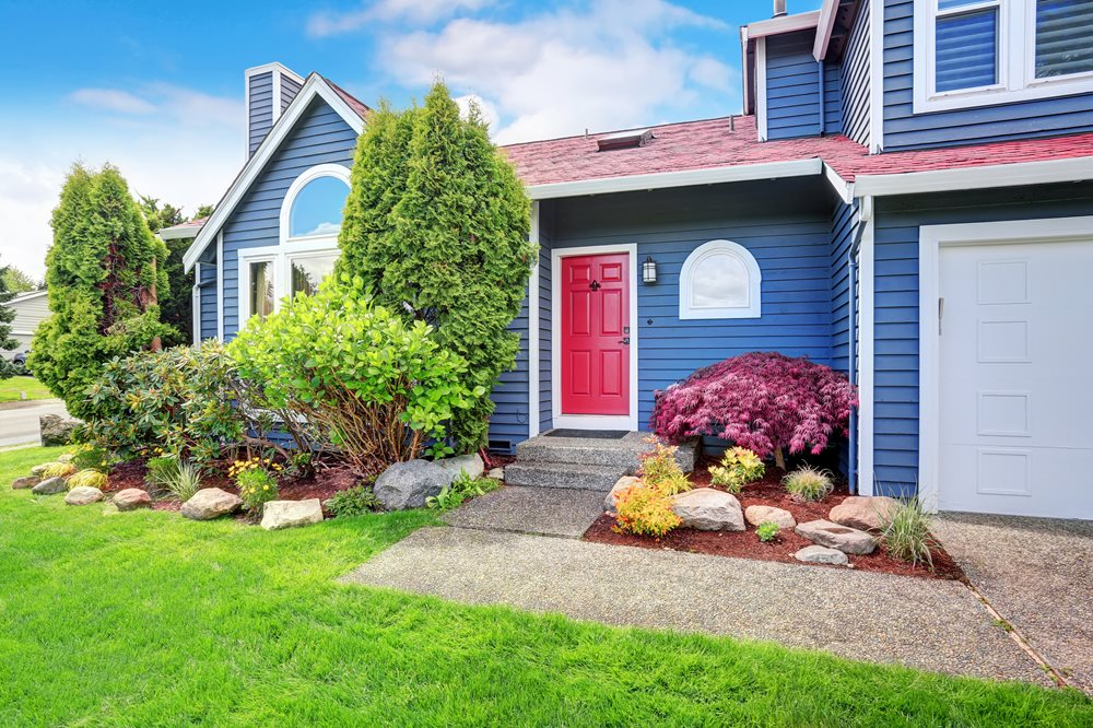 Beautiful curb appeal with blue exterior paint and red roof.
